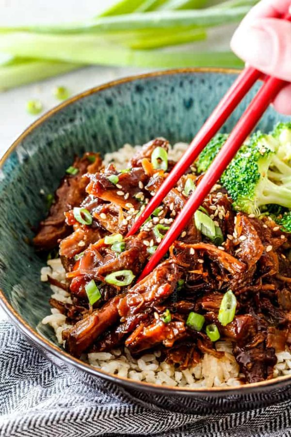 eating Vietnamese Caramelized Pork in green bowl with chopsticks