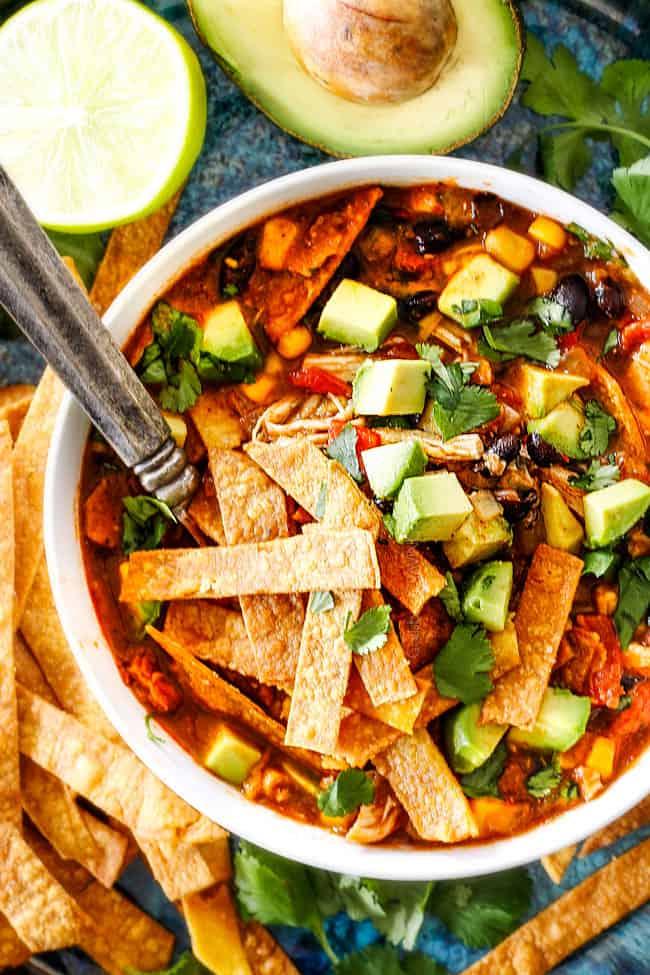 a white bowl of Chicken Tortilla Soup loaded homemade tortilla strips, avocados, sour dream