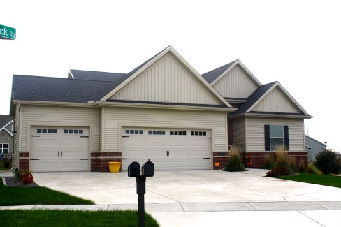 Black roof, vertical siding in gables, carriage style garage door, tan siding
