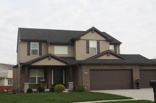 house with tan siding, tan vertical siding, dark brown roof, dark brown brick, brown garage doors