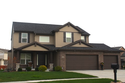 mastic-ovation-in-pebblestone-clay-siding-decorative-gable-accents-musket-brown-trim-and-garage-door-normal-il-blackstone