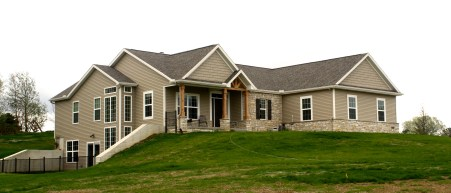 Sprawling ranch with tan siding, tan shakes, cedar porch beams, stone from, brown roof