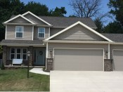 two story home with pebblestone clay siding and shakes, white trim and weathered wood roof with tan garage door, dark brown brick