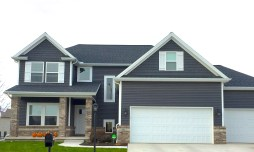 two story home with dark grey siding, shakes, white trim, contemporary garage door and tan brick