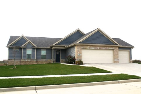 lighter blue siding, dark blue shakes, ranch style home, light tan brick with stone accents light colored garage door