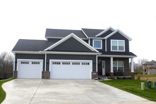 two story dark grey house with white trim and black roof and white garage doors