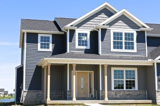 Deep granite shakes and Board and Batten siding with Natural Slate siding, white trim and black roof in Savoy IL