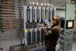 Taylor Wilson operates the scintillation spectrometer next to water sampling equipment at B Reactor.