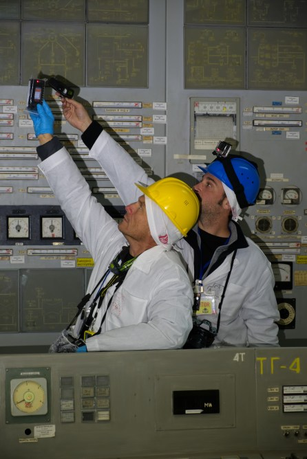 Two visitors investigate the notable radiation hot spot in the Unit 2 control room.