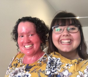 Two women smiling at the camera. One has a red face and curly dark hair and is wearing a yellow dress. The otherness has a white face, glasses and and straight brown hair.