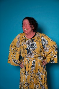 Image: woman wearing long flowing yellow floral dress, standing with her hands on hips in front of a bright blue wall. Her face is red and her hair is short, dark and curly. She is looking to the side and laughing.