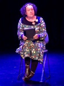 Image: woman with red face and short dark curly hair sitting on a dark stage. She's holding an iPad and speaking. She's wearing a green floral dress and boots. One foot is on top of the other. Pic by Jess Healy Walton.