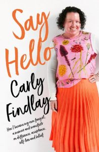 Book cover featuring woman with red face and shirt dark curly hair, smiling. She's wearing a pink floral top and bright orange skirt. The orange text reads Say Hello, and black text reads Carly Findlay. How I became the fangirl of my own story - a memoir and manifesto on difference, acceptance, self love and belief.