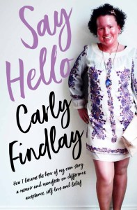 Book cover mock up - woman with red face and short dark curly hair, standing smil8jg. She's wearing a purple and white floral dress and is holding a pink bag. Her legs are bare. The text reads Say Hello, Carly Findlay. How I became the fangirl of my own story -a memoir and manifesto on difference, acceptance, self love and belief