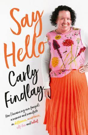 "a book called Say Hello by Carly Findlay. The book cover features woman with red face and short dark curly hair, smiling. She's wearing a pink floral top and bright orange skirt. Her hand is on her hip. Curly orange text reads ""Say Hello"", and black text reads ""Carly Findlay How I became the fangirl of my own story - a memoir and manifesto on difference, acceptance, self love and belief""."