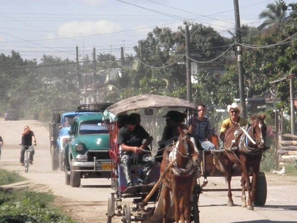The streets of Placetas, Cuba filled with people on bikes, cars, tractors, and horse drawn carriages.