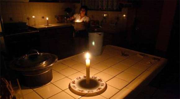 Woman preparing dinner in her kitchen in the dark