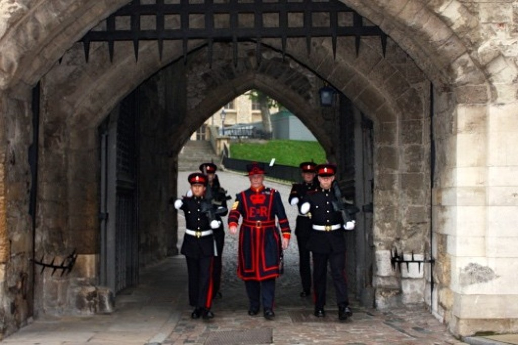 Chief Yeoman Warder of the Tower carrying in one hand the Queen's Keys, walking with members of the duty regiment Foot Guards.