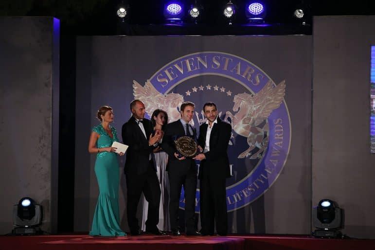 Prince Massimiliano della torre e Tasso and Khalil El Mouthy presenting the award toJohn Georgakakis CEO of the Ecali Club SA