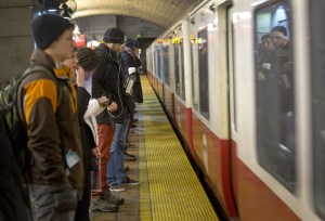 People wait to board a Red Line train at Porter Square MBTA station in February. (Robin Lubbock/WBUR)