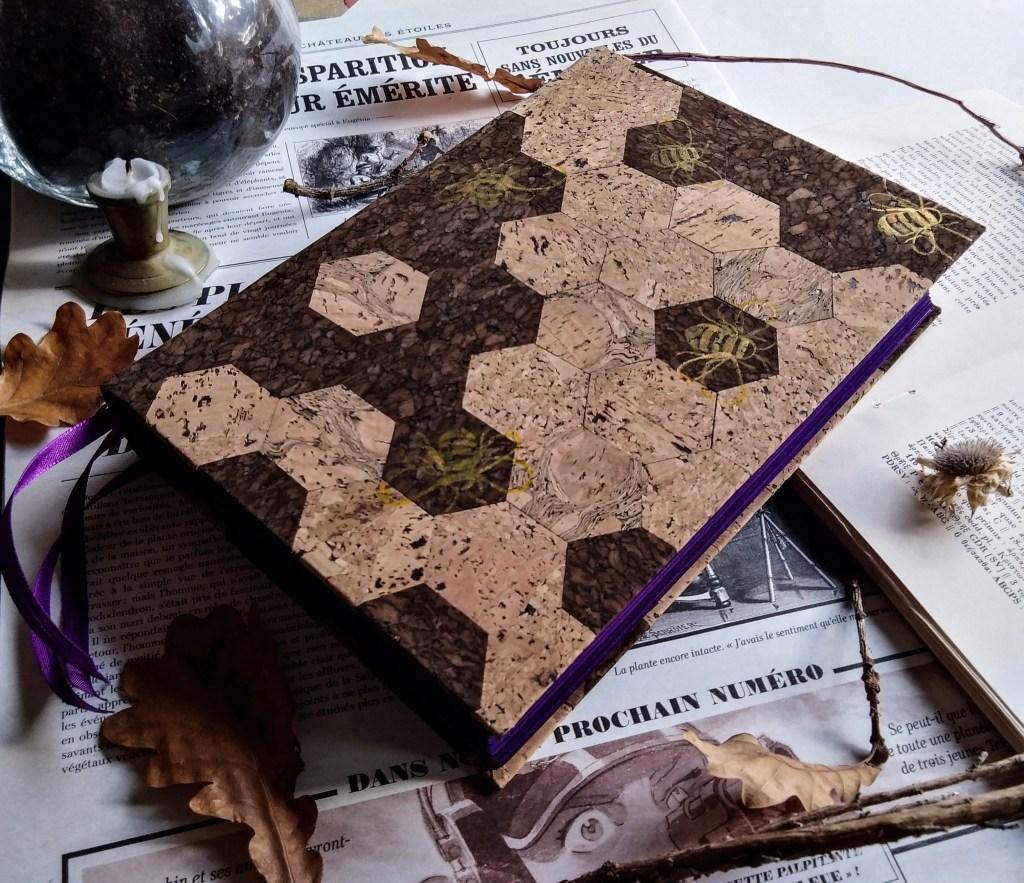 Photo d'un grimoire décoré d'alvéoles en liège découpées à la main, et d'abeilles peintes à l'or.