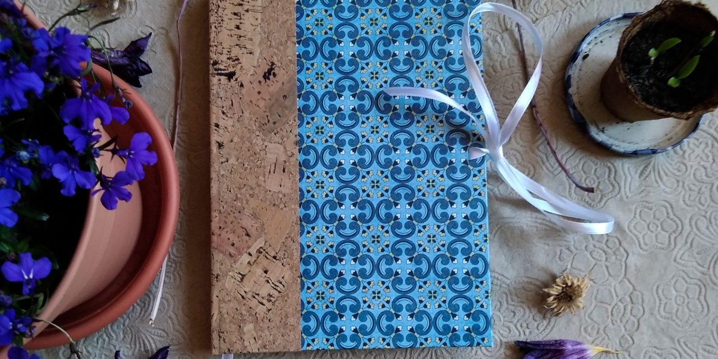 Herbier avec un dos en liège, un papier de couverture à motifs géométriques bleus, et deux rubans de fermeture blancs.