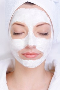 young female face with cosmetic mask - beauty salon