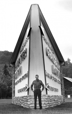 Architect Charles Hartman stands at the iconic Linville sign he designed for Grandfather Mountain. Hartman also designed the Mile High Swinging Bridge. Photo by Hugh Morton and courtesy of the Grandfather Mountain Stewardship Foundation. Click to view full-size image.