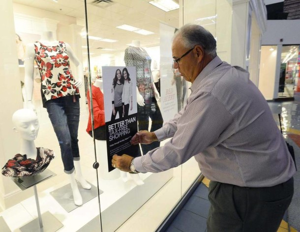 "Ray Soporowski, mall manager for Concord Mills, puts up a ""better than tax-free shopping"" sign on the front window of the Dressbarn at Concord Mills this week. The Dressbarn will participate in the upcoming ""better than tax-free shopping"" event Friday through Sunday. Robert Lahser/Charlotte Observer"