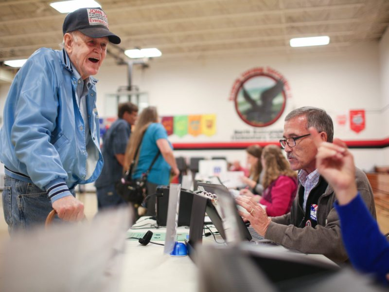 Joseph Brown laughs with election workers as he signs in to vote at North Buncombe Elementary School in Weaverville on Tuesday. Colby Rabon / Carolina Public Press