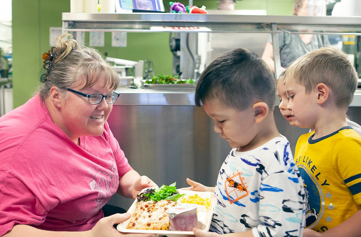 Nutritionist in Cashiers serves lunch to pre-K students.