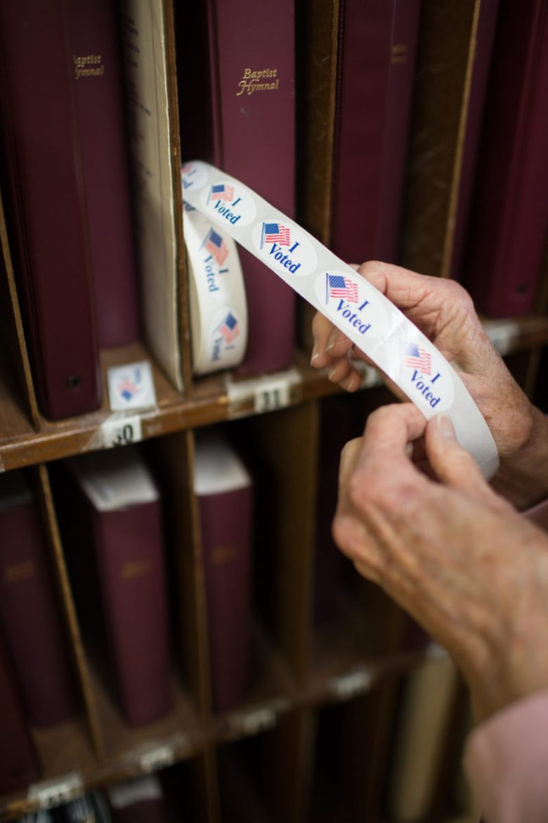 "An poll worker pulls out a ""I voted"" sticker at the First Baptist Church of Black Mountain polling place in Buncombe County on March 3, 2020. Colby Rabon / Carolina Public Press"