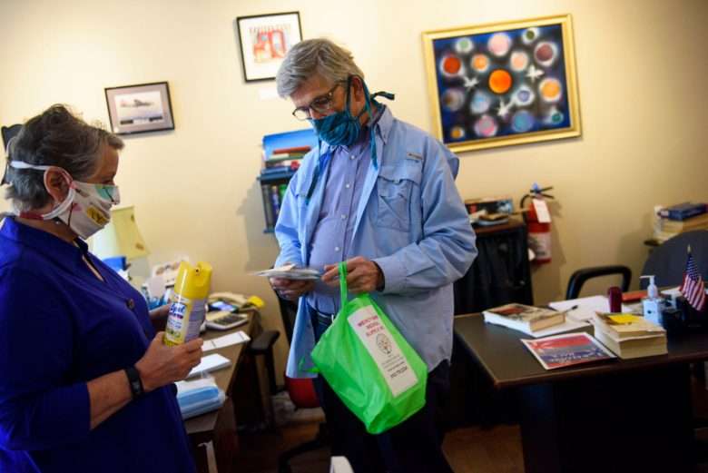 Hank Parfitt, right, brings a can of lysol and newly purchased masks to his wife Diane Parfitt for the reopening of her book store City Center Gallery & Books in Fayetteville on Monday. Melissa Sue Gerrits / Carolina Public Press
