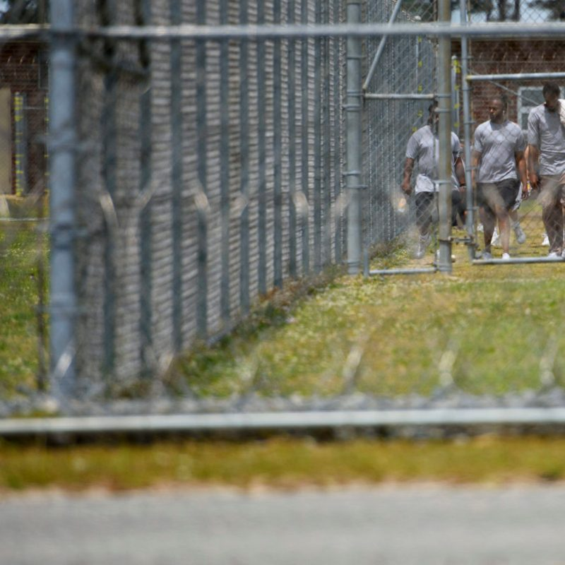 Inmates at Neuse Correctional Institution walk outside behind fences in Goldsboro on May 15. The prison has been the site of a major outbreak of COVID-19. Lawyers for the ACLU and N.C. Department of Public Safety argued in court Wednesday about the effectiveness of the state's protection of prisoners during the pandemic. Melissa Sue Gerrits / Carolina Public Press