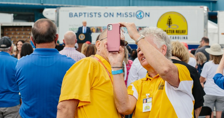 Mills River, NC -- August 24, 2020 A couple takes a selfie as President Donald J. Trump speaks at Flavor 1st Growers and Packers in Mills River, North Carolina on Monday, August 24, 2020. President Trump delivered remarks on the Farmers to Families Food Box Program after touring the Flavor First facility. CREDIT: Jacob Biba for Carolina Public Press