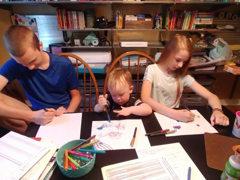 Two of Raleigh mom Laina Yeisley's children work on their homeschool studies, joined by their younger sibling. She is the founder of the Triangle Homeschool Resource Center. Photo courtesy of Laina Yeisley