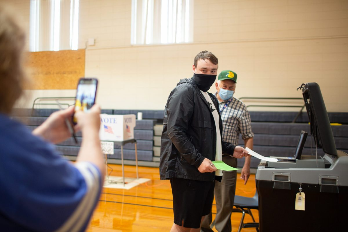 Jamie Osteen takes a photo as her son Nolan, a first-time voter, puts his ballot in the scanner to be counted at Upward Elementary School in Henderson County on Election Day. Colby Rabon / Carolina Public Press