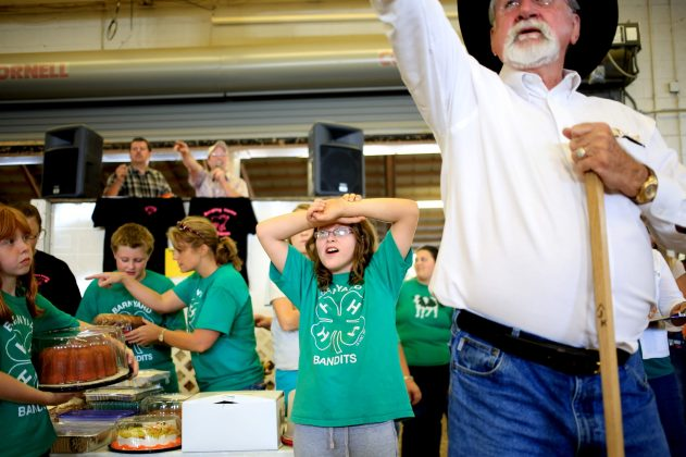 Lauren Thomas, 10, looks on as Jerry King signals to a winning bidder at the start of the 4-H Livestock benefit auction on Saturday, Sept. 23, 2012. In addition to livestock, the auction featured cakes, plants, saddles and horse gear. Over $7,500 was raised to benefit the clubs. Photo by Colby Rabon.