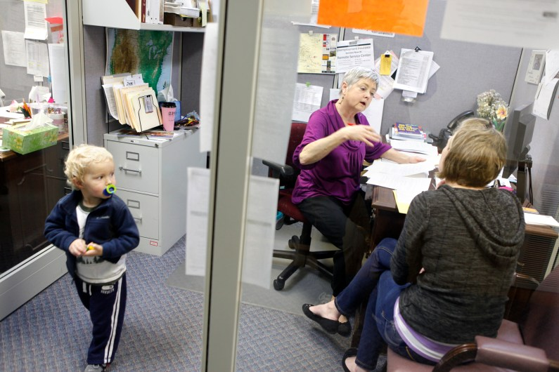 Ellen Forcier, Employment Consultant speaks with Jordan Berger, right, who is looking for health care work at the Hendersonville JobLink Career Center. Berger's son Caleb, 3, is at left. (Matt Rose / Carolina Public Press)