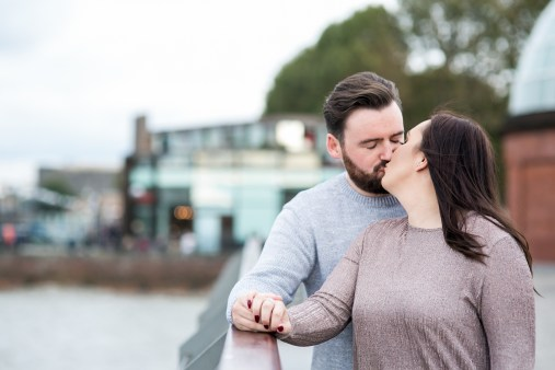 Brunette engaged couple kissing next to the Thames in Greenwich