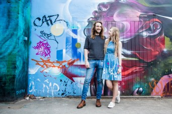Couple in front of blue and pink street art on Brick Lane