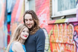 Natural photo of couple smiling at camera against street art graffiti