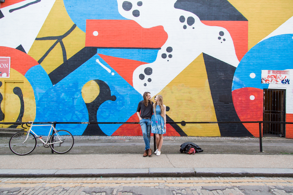 A couple stood in front of a red, yellow and blue mural on Chance Street, Shoreditch