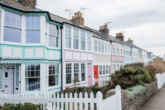 Colourful row of houses and white picket fences on Whitstable seafront