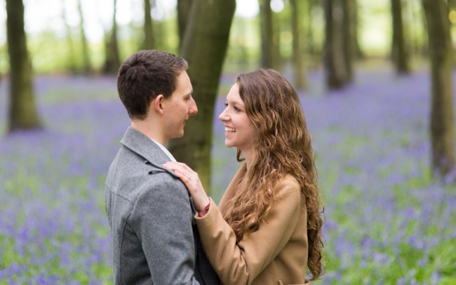 Couple smiling at each other in bluebell woods