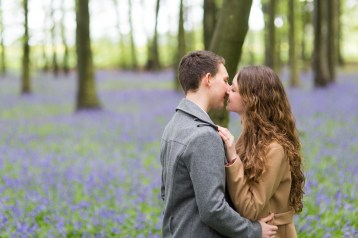 Couple kissing amongst bluebells in Harpenden woods