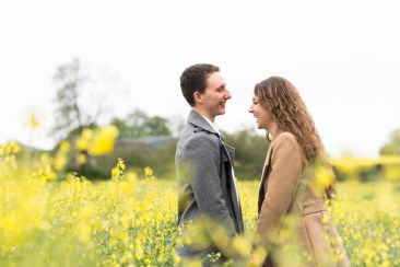 Couple holding hands and laughing in yellow rapeseed field