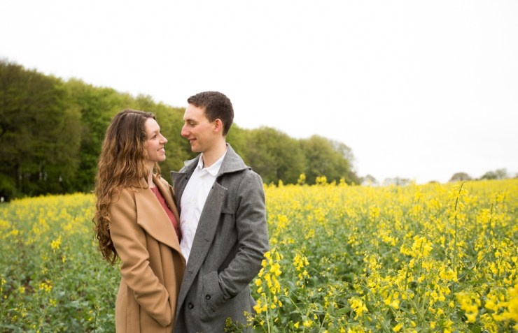 Couple stood in yellow rapeseed field smiling at each other
