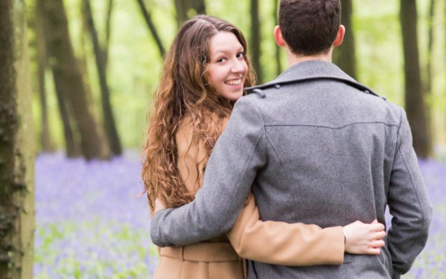 Couple walking naturally through bluebell woods