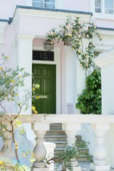 Pastel pink home with olive front door and rose plant around it